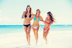 Beautiful Happy Girls on the Beach. Group of Three Beautiful Attractive Young Women Walking on the Beach Royalty Free Stock Photography