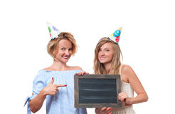 Beautiful happy girls with gift box at celebration birthday party. Beautiful happy girls in a celebratory cap with gift box at celebration party. Birthday Royalty Free Stock Photos