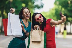 Beautiful happy girls in sun glasses holding shopping bags, making selfie on smart phone and smiling. Sale and. Beautiful girls in sun glasses holding shopping stock image