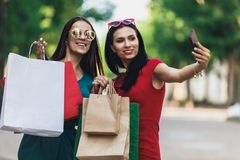 Beautiful happy girls in sun glasses holding shopping bags, making selfie on smart phone and smiling. Sale and. Beautiful girls in sun glasses holding shopping royalty free stock photography