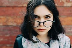 Beautiful happy hipster girl goes in the city. Closeup of trendy girl face. Stock Image