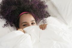 Beautiful Happy Hispanic Teen Waking Up And Smiling Undercover. Portrait of happy black girl looking at camera undercover. Young African American woman waking up Royalty Free Stock Photo