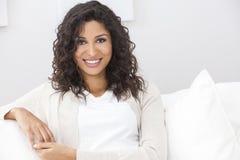 Beautiful Happy Hispanic Woman Smiling. Portrait of a beautiful young Latina Hispanic woman smiling with perfect teeth sitting on a white sofa Stock Photo