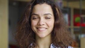 Beautiful happy hispanic young adult 20s woman looking at camera, headshot.