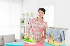 Happy housewife sort out family clean clothing. Beautiful happy housewife sort out family clean clothing with iron on ironing board in living room and looking at Stock Photos