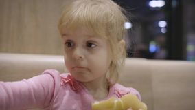 Beautiful happy hungry baby girl eating hamburger. Concept child with fast food stock footage