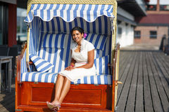 Beautiful happy indian bride sitting in beach chair Royalty Free Stock Photos