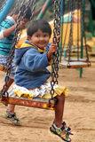 Beautiful &  happy indian girl(child) playing on a swing in park Royalty Free Stock Image