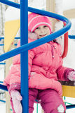 Beautiful happy kid in the red jacket. In the winter outdoors royalty free stock image