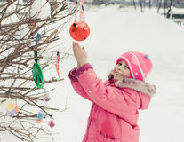 Beautiful happy kid in the red jacket. In the winter outdoors stock image