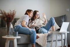 Beautiful happy lesbian couple sitting on sofa at home with pet dog bassengi online chatting using laptop, happy family