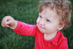 Beautiful happy little baby girl sitting on a green meadow Royalty Free Stock Photography