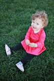 Beautiful happy little baby girl sitting on a green meadow Royalty Free Stock Image