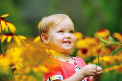 Beautiful happy little baby girl sitting on a green meadow with Stock Images