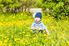 Beautiful happy little baby girl sitting on a green meadow with yellow flowers dandelions on the nature in the park. Royalty Free Stock Images