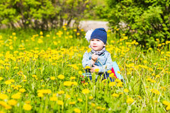 Beautiful happy little baby girl sitting on a green meadow with yellow flowers dandelions on the nature in the park. Stock Photo