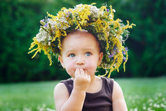 Beautiful happy little baby girl in a wreath on a meadow on the nature Stock Images