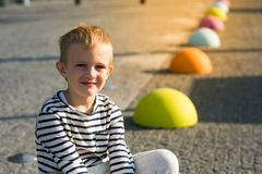 Beautiful happy little boy sitting on colored stones, looking at camera Royalty Free Stock Photography