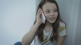 Beautiful happy little girl emotional talking on the smartphone by window. stock video