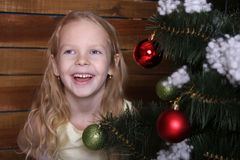 Beautiful happy little girl laughing near the Christmas tree. 