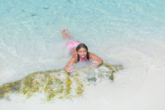 Beautiful happy little girl lying and relaxing on the beach in ocean water. Nice beautiful happy little girl lying and relaxing on the beach in ocean water on Royalty Free Stock Photo