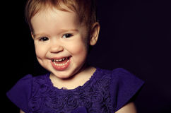 Beautiful happy little girl in a purple dress Royalty Free Stock Images