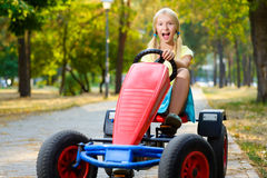 Beautiful happy little girl riding toy car in Royalty Free Stock Photography