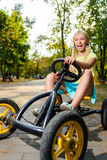 Beautiful happy little girl riding toy car in Stock Photo