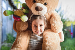 Beautiful and happy little girl with teddy bear on her shoulder Royalty Free Stock Photos