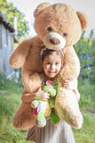 Beautiful and happy little girl with teddy bear on her shoulder Stock Image