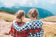 Beautiful happy little girls in mountains in the background of fog royalty free stock images