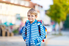 Little kid boy with school satchel on first day to school. Beautiful happy little kid boy with glasses and backpack or satchel on his first day to school or Royalty Free Stock Photography