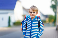 Little kid boy with school satchel on first day to school. Beautiful happy little kid boy with glasses and backpack or satchel on his first day to school or Stock Images
