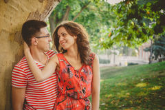 Beautiful happy loving couple in red clothes on nature under a big tree embracing and looking at each other.  Stock Image