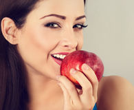 Beautiful happy makeup woman holding red tasty apple and biting Stock Images