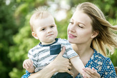 Beautiful happy mather with baby boy outdoor on nature Royalty Free Stock Photos