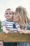 Beautiful happy mather kissing her baby son outdoor on a bench. Portrait of beautiful happy mather with baby outdoor, on nature Stock Images