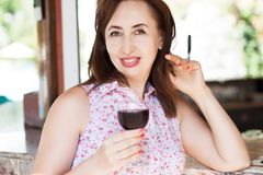 Beautiful happy middle aged woman holds a glass of wine at the resort on her vacation, summer concept holidays.  royalty free stock photography