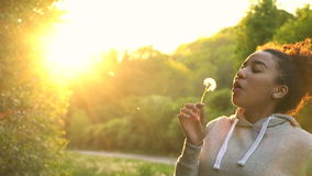 Beautiful happy mixed race African American girl teenager or young woman laughing, smiling and blowing a dandelion stock footage