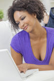 Mixed Race African American Girl Using Laptop Computer. A beautiful happy mixed race African American girl or young woman laying down on sofa using a laptop Royalty Free Stock Photo