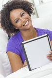 Mixed Race African American Girl Using Tablet Computer. A beautiful happy mixed race African American girl or young woman laying down on sofa using a tablet Stock Photos