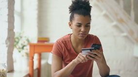 Beautiful happy mixed race woman online banking using smartphone shopping online with credit card at home lifestyle