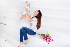 Beautiful and happy mom brunette in white t-shirt and jeans throws up a little smiling baby daughter on a white background with t royalty free stock image