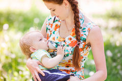 Beautiful happy mother breastfeeding outdoor Stock Photo