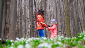 Beautiful happy mother and cute daughter having fun and jumping through the spring forest full of snowdrops, in a sunny stock video footage