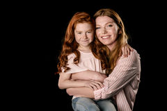 Beautiful happy mother and daughter hugging and smiling at camera Royalty Free Stock Image
