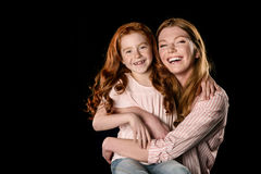 Beautiful happy mother and daughter hugging and smiling at camera Royalty Free Stock Images