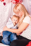 Beautiful happy mother hugging baby on a bed. Beautiful happy mother hugging a baby on a bed in the bedroom Stock Images