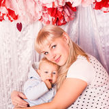 Beautiful happy mother hugging baby on a bed. Beautiful happy mother hugging a baby on a bed in the bedroom Royalty Free Stock Photography
