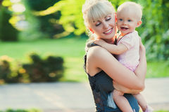 Beautiful happy mother hugging baby girl with love outdoors summer background Stock Image